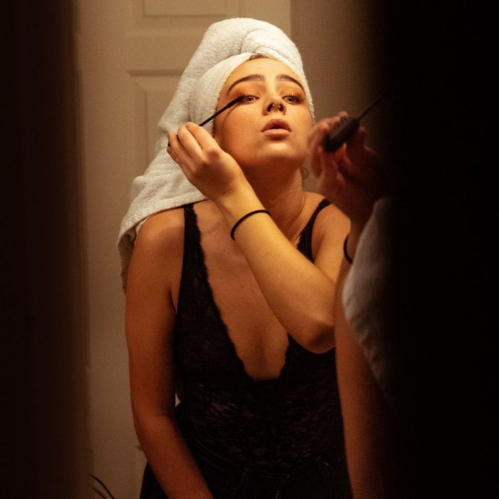 Woman applying makeup with towel on her head