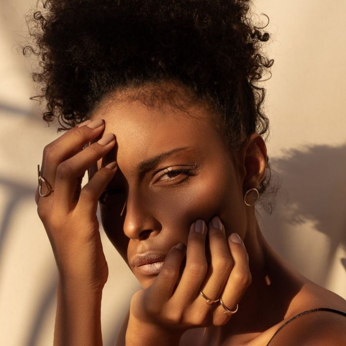 A woman with her hands posed against her face