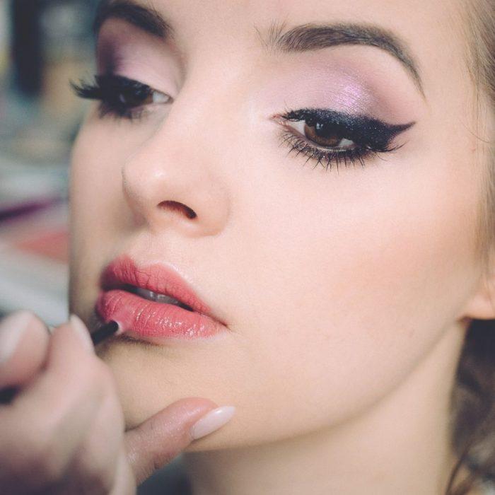 woman having lip liner applied